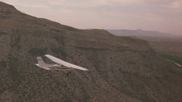 a-a aerial tracking shot l-r of small propeller airplane flying over desert landscape. plane flies over desert canyons, cliffs, plateaus and mountains  with sparse vegetation. plane flies over river and valley. mountains in bg. air-to-air. - propeller video stock e b–roll
