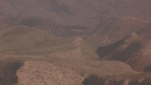 g-a wide angle tracking shot of small propeller airplane flying over desert landscape. plane flies over desert canyon with sparse vegetation. mountains in bg. ground-to-air. - propeller video stock e b–roll