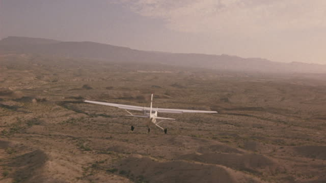 a-a aerial tracking shot following straight behind small propeller airplane flying over desert landscape. plane flies  over desert hills and valleys. mountains in bg. air-to-air. - propeller video stock e b–roll