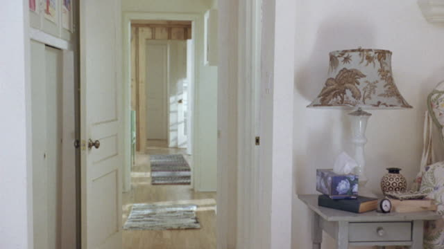 medium angle of open door looking out from bedroom into hallway. see clock, books, tissue, and lamp on gray bedside table with drawer at right. see floral lampshade on lamp. see partial floral bedspread on bed at right. see mats or carpets on wooden floor - bedroom doorway stock videos & royalty-free footage