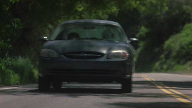 MEDIUM ANGLE DRIVING POV IN FRONT OF GRAY FORD TAURUS BEING CHASED BY BLACK SUV. SEE BLACK SUV SWERVING BEHIND GRAY TAURUS. DRIVING THROUGH COUNTRYSIDE.