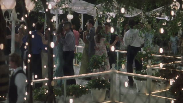 vídeos de stock e filmes b-roll de pan left to right of formal dinner party or celebration in back patio next to pool. see guests dressed in formal wear, chatting and sitting at tables. see gazebos set up around pool with white draperies. - formal garden