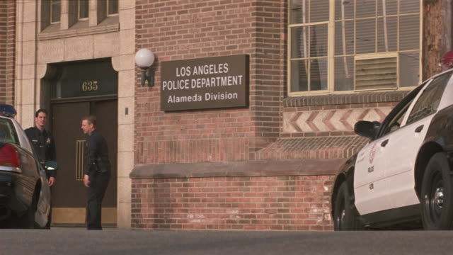 medium angle of los angeles police station during day. see police cars and police motorcycles parked outside. see two police officers chatting outside. - police car stock videos and b-roll footage