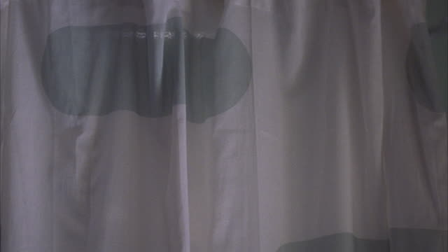 medium angle of shower in bathroom. shower curtain with green spots. floral wallpaper. pan up to see shower head above curtain rack. - shower curtain stock videos and b-roll footage