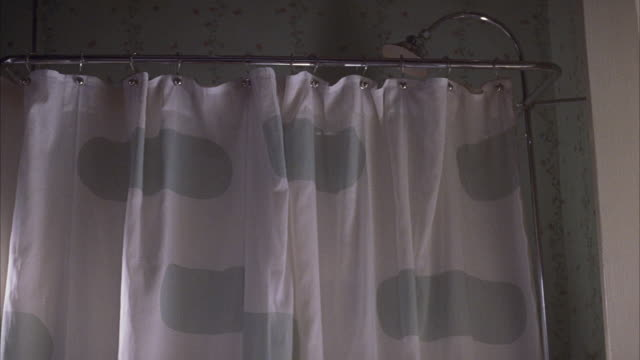 medium angle of shower curtain with green spots in bathroom. curtain flutters in breeze. - shower curtain stock videos and b-roll footage