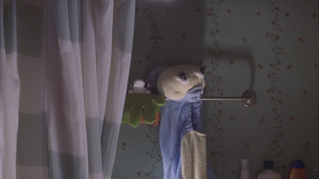vídeos de stock, filmes e b-roll de medium angle of  shower curtain with green spots pulled open revealing wash cloth or toy fish  hanging next to gloves on rack. - banheiro estrutura construída