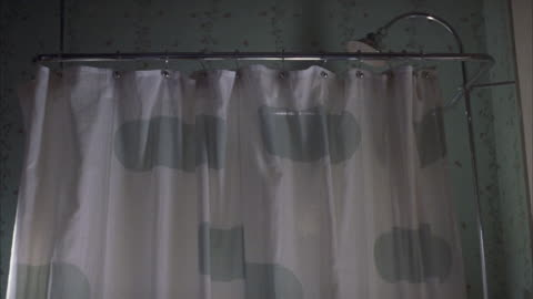 medium angle of shower in bathroom. shower curtain with green spots. floral wallpaper. pan up to see shower head above curtain rack. - bathroom stock videos & royalty-free footage