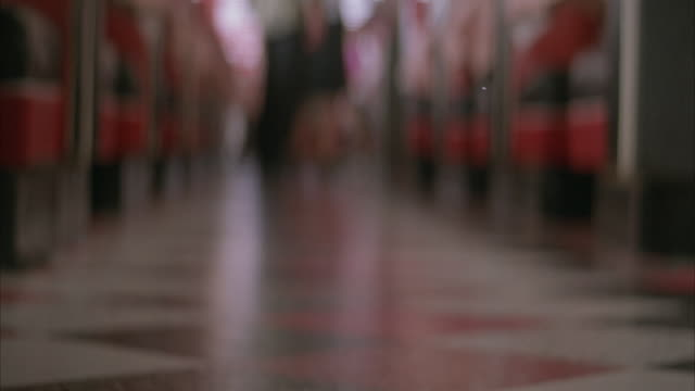 medium blurred angle of walkway between rows of red booths in diner or restaurant. see female legs in white socks and sneakers walk away from pov. pan up body to see waitress in black skirt, white polo, and blue apron holding tray. see waitress bend over - servitris bildbanksvideor och videomaterial från bakom kulisserna