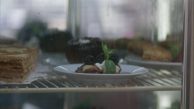 medium angle of desserts on rack in display refrigerator. could be in restaurant or diner. see waitress open glass door and take out dessert with blackberry topping. see waitress holding dessert exit right. see second waitress using touch-screen register - dessert topping stock videos & royalty-free footage