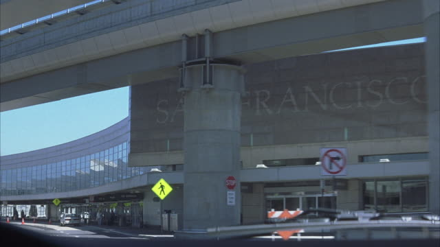 "process plate driving from high pov into san francisco airport. see pov drive  in lane reading ""south terminal"", listing airlines ""alaska america west ata continental delta northwest twa us airways"". see stone face terminal at right reading ""san francisco - twa video stock e b–roll"