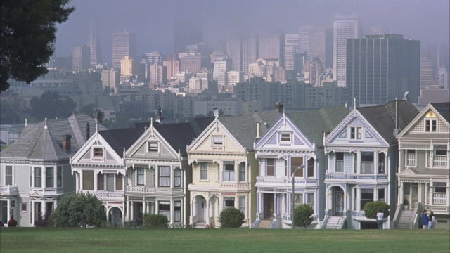 MEDIUM ANGLE OF VICTORIAN ROW HOUSES AT ALAMO SQUARE PARK. SEE SAN FRANCISCO CITY SKYLINE IN HAZY BACKGROUND. SEE PEDESTRIANS AT RIGHT.