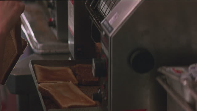 medium angle of woman putting two pieces of bread into revolving toaster. see containers of jam in foreground. insert. - toaster appliance stock videos & royalty-free footage