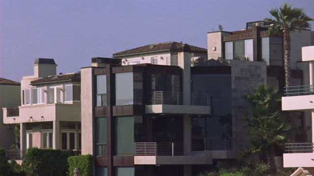 """medium angle of modern multi-story upper class houses. could be beach houses. see balconies and floor length windows on all floors. see plants fluttering in breeze. see clear blue sky.<p><a href=""""https://www.sonypicturesstockfootage.com/footage?kid=4366""""> - floor length</a></p> stock videos & royalty-free footage"""
