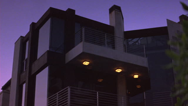 up angle of modern multi-story upper class house or apartment building. could be beach house. see floor-length windows on all floors and brown trim. see beige balconies with metal railings. see green leaves of plant in right foreground. see rectangular li - floor length stock videos & royalty-free footage