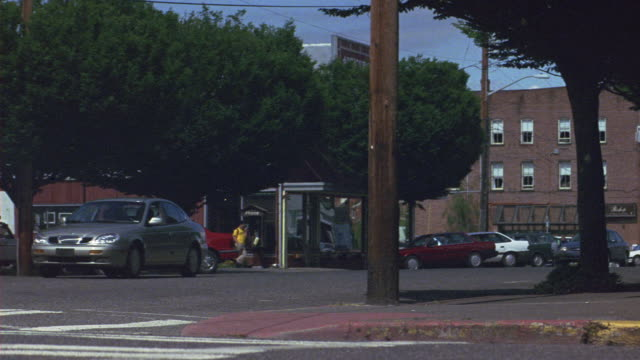 """vídeos de stock, filmes e b-roll de medium angle city street corner in suburbs. see cars parked on side of street. see wood paneled building in background. see brick wall and brick building in right foreground. see gray ford taurus swerve to make left turn on city street past """"art & antique - antiquário loja"""