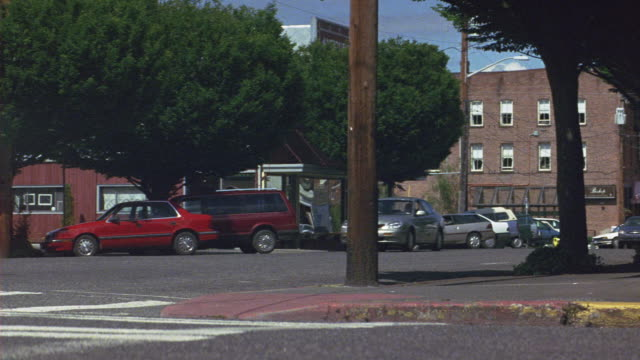 """vídeos de stock, filmes e b-roll de medium angle city street corner in suburbs. see cars parked on side of street. see wood paneled building in background. see brick wall and brick building in right foreground. see gray ford taurus swerve and fishtail to make left turn on city street past """" - antiquário loja"""