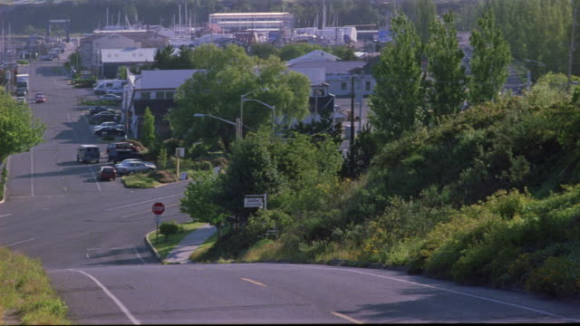 medium angle from peak of hilly suburban street. see gray ford taurus followed by black cadillac escalade turn onto street from left. could be car chase. see cars drive towards and past pov right. neg cut. - キャデラック点の映像素材/bロール