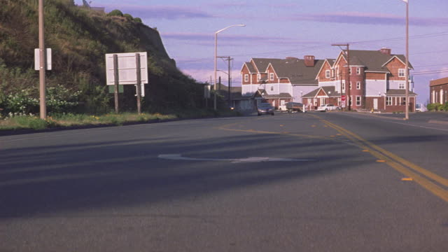 medium angle of small town city street. see three story brick buildings in background. could be houses or apartment buildings. see gray ford taurus speed toward pov followed by black cadillac escalade. see cars turn right to drive up hill. see upper middl - middle class stock videos & royalty-free footage
