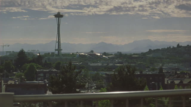 medium angle of the city of seattle with space needle in background. see puffy white clouds in blue sky. see mountain range in background. see various greed trees. see various multi-story buildings in city. pov moves to right as camera moves on car. see s - スペースニードル点の映像素材/bロール