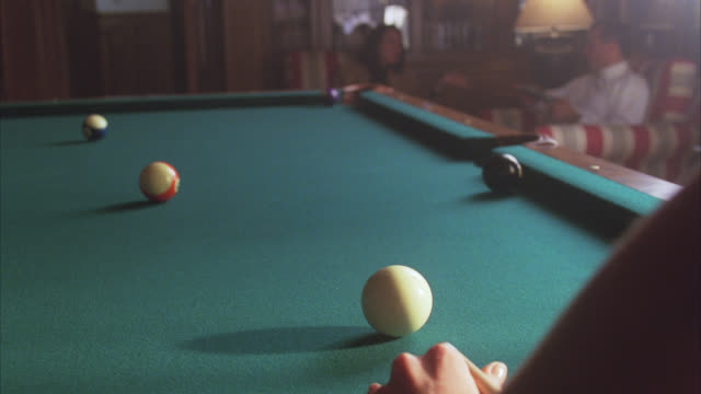 CLOSE ANGLE OF POOL CUE HITTING BALL. POOL TABLE, BILLIARDS. GAMES.