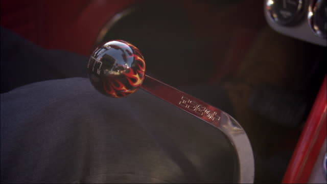 """close angle of classic car stick shift. stick shift knob is a black ball with red and orange flames rising from the bottom. brand name """" hurst"""" is printed on metal extension of shifter. see clutch pedal in background. man's hand shifts gears while his fee - pedal stock videos & royalty-free footage"""