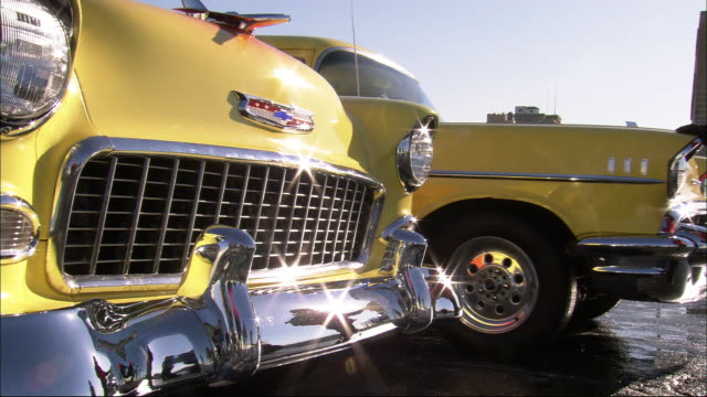 stockvideo's en b-roll-footage met close angle of radiator grille and hood of 1950's era chevrolet bel air. gleaming chrome bumper gleams reflects sunlight. second yellow car pull up to left of first car. classic cars. - bumper