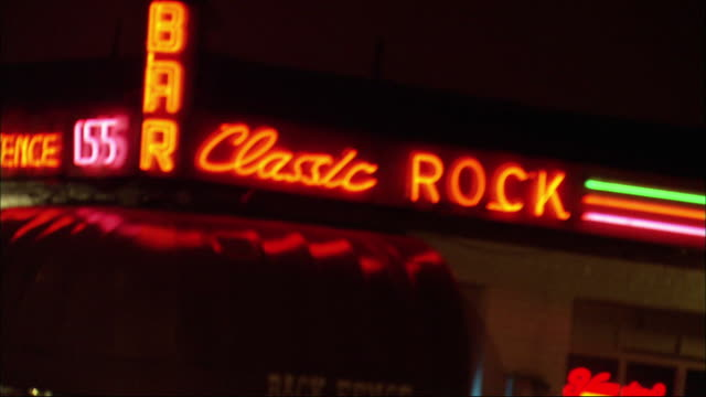 """medium angle of red neon sign that reads """"classic rock bar"""" on building. camera goes out of focus. then returns to focus. see awning beneath sign that reads """"back fence"""". - awning stock videos & royalty-free footage"""