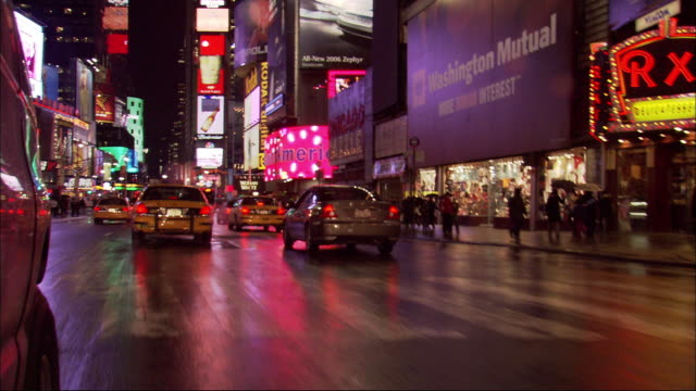 vídeos de stock, filmes e b-roll de hand held shot of streets outside times square at night from driving pov. see colorful billboards. see bright lights of buildings. pedestrians crowd the streets. see yellow taxicabs drive down street. - câmara de mão