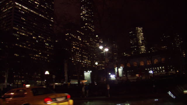 hand held shot of new york city skyline at night from pov of street. see bus pull past street lights. skyscrapers lit in bg. grace building.  see traffic drive by. camera pov tilts then zooms in on lit buildings with many glass windows. see many yellow ta - bryant park stock videos and b-roll footage