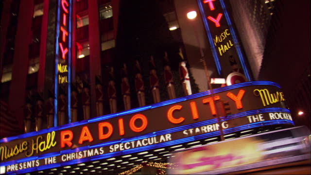 "hand held shot of storefronts from driving pov down new york city street, avenue of the americas. see radio city music hall building with neon signs that read ""radio city""  lit. see trees lit in christmas lights. tall modern skyscrapers or office building - radio city music hall stock videos and b-roll footage"