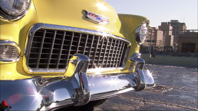 close angle of radiator grille and hood of 1950's era chevrolet bel air. gleaming chrome bumper gleams reflects sunlight. second yellow car pull up to left of first car. classic cars. - bumper stock videos & royalty-free footage