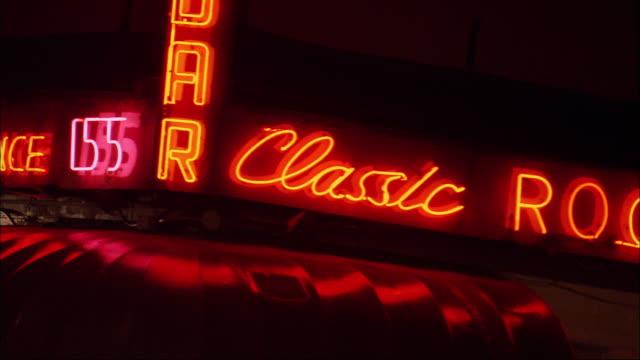 "vídeos de stock e filmes b-roll de hand held zoom in on a neon sign for back fence bar. ""classic rock"". greenwich village. - rock"