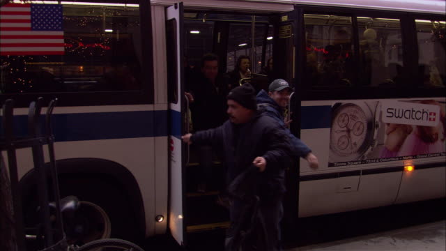 hand held of parked new york city bus at bus stop. see four male passengers exit with bags or backpacks. see doors close. - bushaltestelle stock-videos und b-roll-filmmaterial
