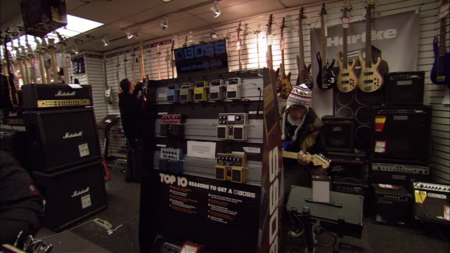 """hand held of inside """"sam ash"""" music store in new york city. see guitars hanging on walls, amplifiers, and speakers on the ground. see people walking around store and a male teenager with a knit cap sitting on stool playing a guitar with a price tag attach - playing tag stock videos & royalty-free footage"""