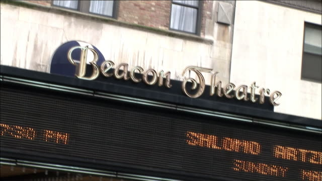 """hand held view of multi-story """"beacon theatre"""" building and marquee in new york city. see taxi drive by. narrow shutter angle effect used giving everything a streaky look. - beacon theatre stock videos and b-roll footage"""