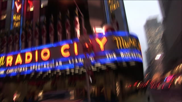 medium angle of radio city music hall lit in neon lights from driving pov. see buildings next to radio city music hall on the corner of the street. pedestrians walk down the sidewalk. cars with headlights on drive past. - radio city music hall stock videos and b-roll footage