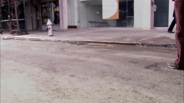 """hand held of the slipper room awning on building. could be apartment building. see front entrance closed with metal curtain. see pov pan right to show """"orchard"""" street sign and brick buildings in the background. see one way sign, back of stop sign and lam - one way stock videos & royalty-free footage"""