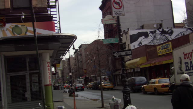 hand held of city neighborhood. see orchard street sign, one way sign, and no left turn sign on lamp post. see zozo's sign on store entrance. see taxi and cars on street frame right. see pedestrian walk frame right. see brick building in background. - one way stock videos & royalty-free footage