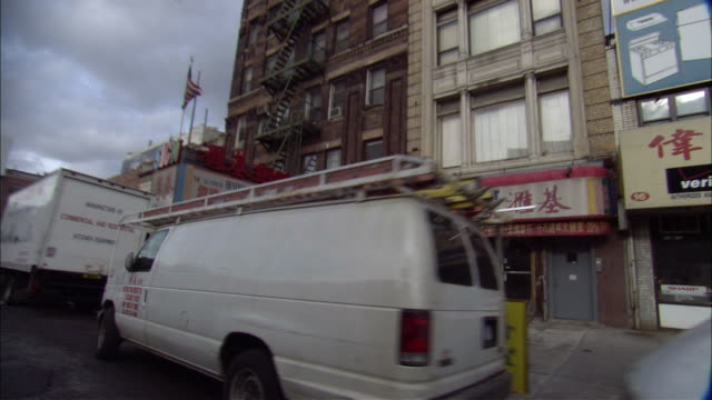 "MEDIUM ANGLE OF NEW YORK STREETS. SEE WHITE VANS PARKED ON SIDE OF STREET. SEE ""VERIZON WIRELESS"" BILLBOARD ON TOP OF BUILDING. SEE BRICK BUILDING WITH FIRE ESCAPE LADDERS ON SIDE. SEE CHINESE CHARACTERS ON SIGN IN FRONT OF BRICK BUILDING. SEE AMERICAN FL"