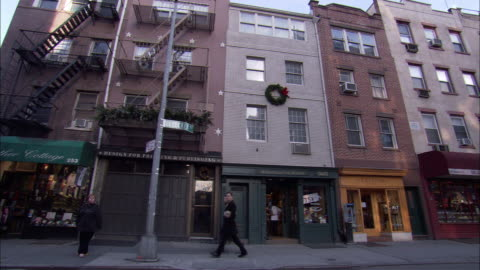 hand held of bleecker street, west greenwich village. see people or pedestrians walking on sidewalk in front of three story brick residential or apartment buildings with shops or stores on first level. see fire escapes and a christmas wreath on buildings. - greenwich village stock videos & royalty-free footage