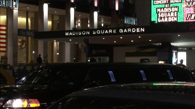vídeos de stock e filmes b-roll de hand held of entrance to madison square garden. see limo drive  up in front of building, stop, then continue left. see chase sign in front entrance. see man walk by pov. see cars, fire truck and taxi in traffic pass by on street. see pedestrians walk on s - madison square garden