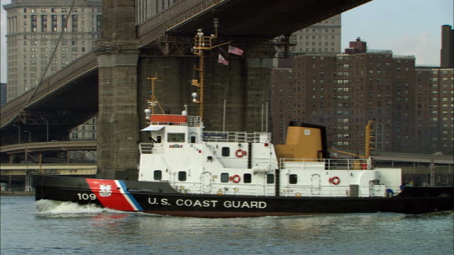 "PAN UP FROM ""U.S. COAST GUARD"" BOAT ON THE EAST RIVER UNDER THE BROOKLYN BRIDGE IN NEW YORK CITY TO BROOKLYN BRIDGE AND BRIDGE TRUSS. SEE MULTI-STORY AND HIGH RISE BUILDINGS AND VERIZON BUILDING IN BG."