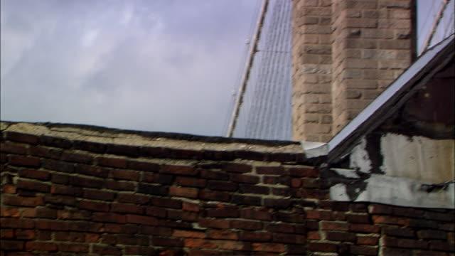 medium angle of flowing american flag on top of brooklyn bridge. pan down along bridge. pan right to left across brick wall of bridge. see  wall ending with ornate wooden corner piece. see top of american international building on left. pan down to brick - brooklyn bridge stock videos & royalty-free footage