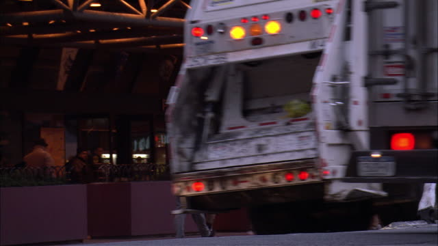 "close angle of garbage truck.  pov zooms out on moving traffic.  see traffic part to display ""port authority bus terminal"" sign.  see pedestrians around entrance of bus terminal. - garbage truck stock videos and b-roll footage"