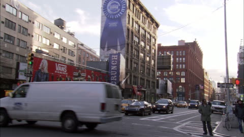 """hand held of multi-story, slender building between two city streets from bleecker street in greenwich village. see """"crunch"""" sign on right side of building. see pedestrians and cars cross through intersection. see newspaper stands on sidewalks. see multi-s - one way stock videos & royalty-free footage"""