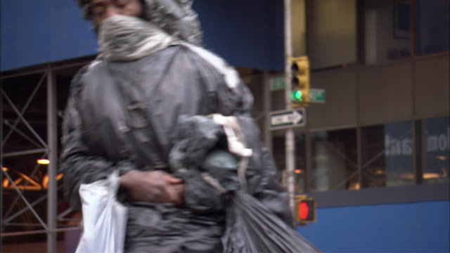 medium angle of man covered in garbage bags crossing crosswalk in front of port authority bus terminal. could be homeless man.  see traffic move once man has crossed.  see multi-story, brown office building to left of port authority bus terminal. - port authority stock videos & royalty-free footage