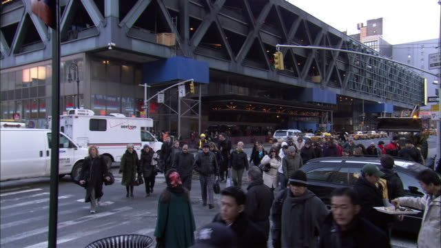 """medium angle of port authority bus station.  see pedestrians walk across crosswalk away from bus station, terminal, towards pov.  see yellow """"cat"""" bulldozer lifting up asphalt.  see construction workers in hard hats and orange vests. - tarmac stock videos & royalty-free footage"""