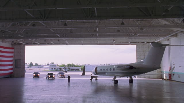wide angle of jet plane parked in airport hangar. three black suburbans drive up to plane and soldiers get out of car. - hangar stock-videos und b-roll-filmmaterial