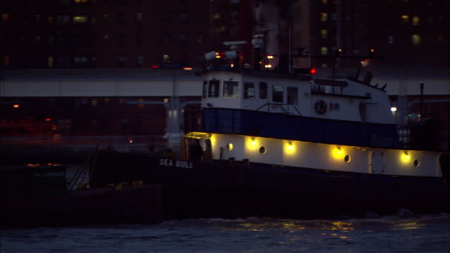MEDIUM ANGLE OF TUGBOAT WITH BLUE AND WHITE STRIPES. SEE TUGBOAT PUSHING LOW, FLAT COMMERCIAL BOAT, COULD BE OIL TANKER IN EAST RIVER. PULLS BACK TO MEDIUM UP ANGLE OF BROOKLYN BRIDGE. SEE WHITE LIGHTS ALONG BRIDGE. SEE MULTI-STORY OFFICE OR APARTMENT BUI