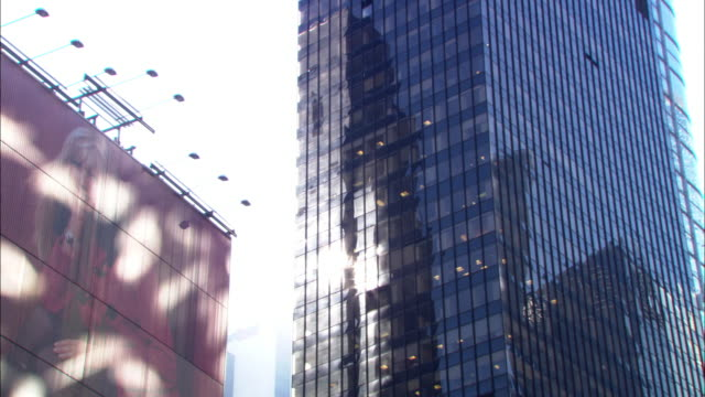 medium angle of modern style,  mid-century, glass and steel rectangular, multi-level office building next to the virgin records store in times square.  could be new york times tower.  see blond-haired female model on billboard to right.  pov move in and o - sony stock videos & royalty-free footage